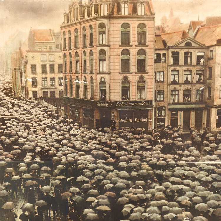 A photograph of a city street, crowded with people holding black umbrellas