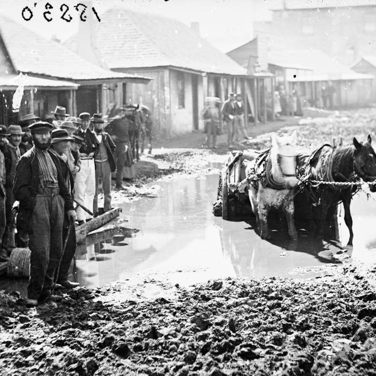 Horse and cart struggling through muddy street as men watch