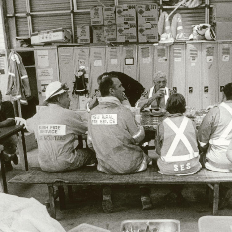 Off-duty firemen eating food together at table