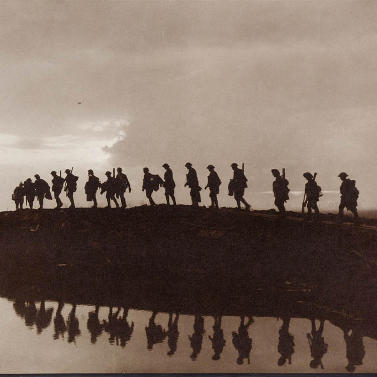 Men in silhouette walking along duckboards in the western front, 1917.