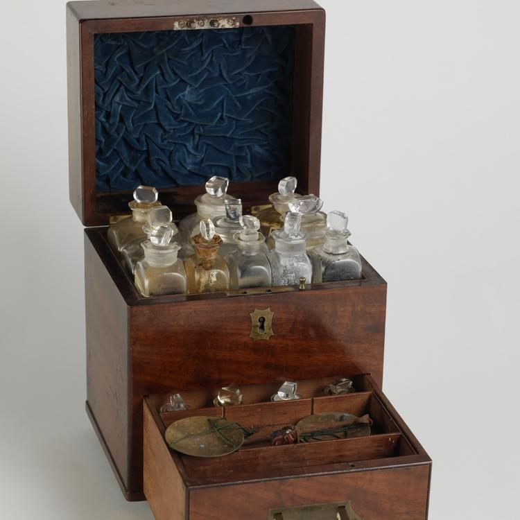 wooden box containing glass medicine bottles