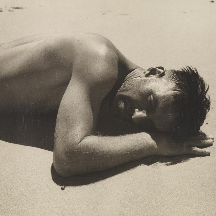 A sepia photograph of a man lying on a beach, covered in droplets of water