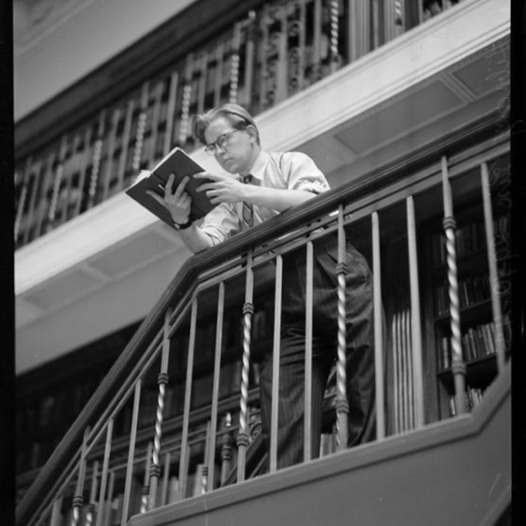 Man leaning on railing reading a book