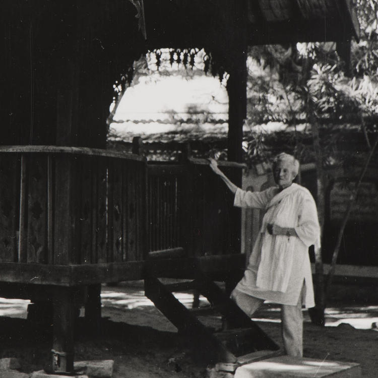 A black and white photograph of an older woman standing next to a hut, resting her hand on the banister.
