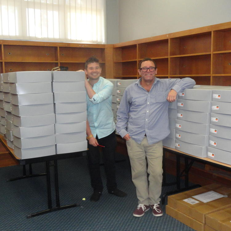 A man and a boy smiling, in front of a number of grey boxes