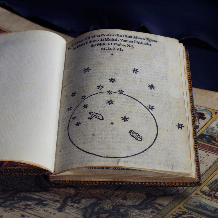 A sketch of a star constellation in an old printed book, propped up on a map.