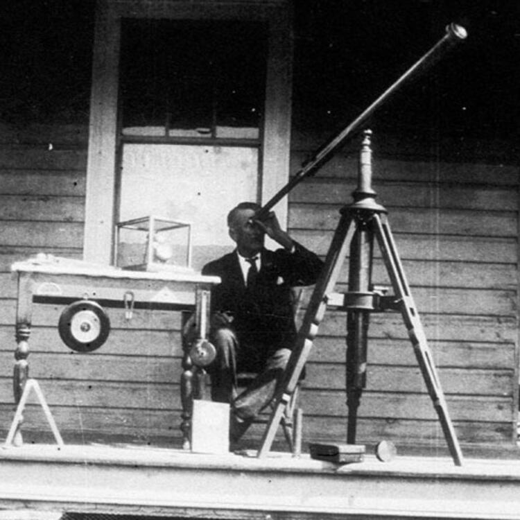 A man sitting on a veranda, looking through a telescope