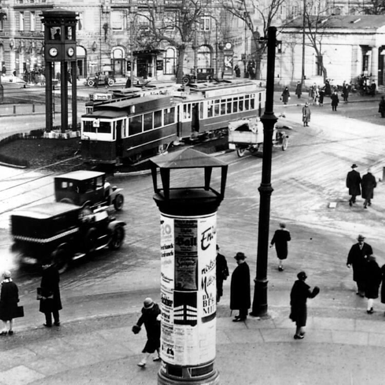 black and white image of a city street in Berlin full of traffic and people in 1927