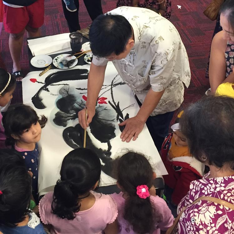Artist demonstrating Chinese painting techniques to a group