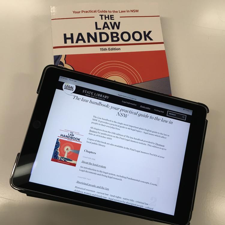A large law book with an iPad on top