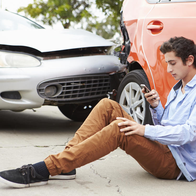 Young man sitting on the road in front of two cars that have had an accident