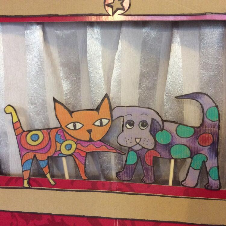 A cardboard box puppet theatre with cat and dog puppets
