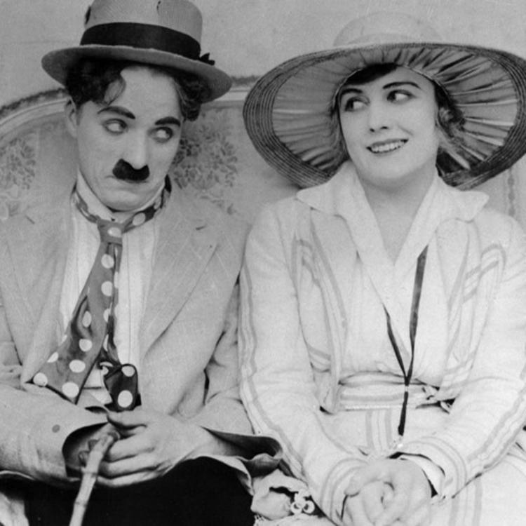 Charlie Chaplin and a woman sitting on a couch looking at each other