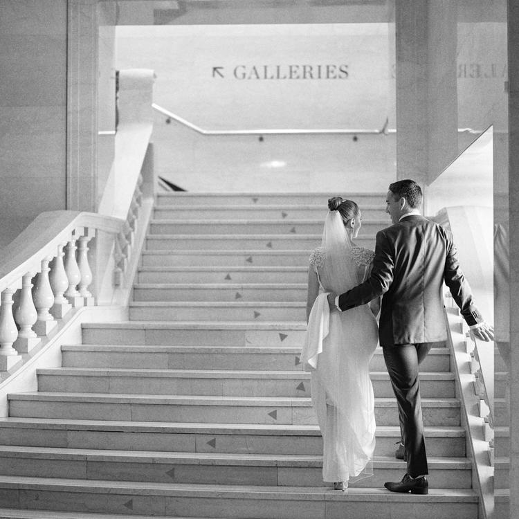 Image of a bride and groom on marble staircase.