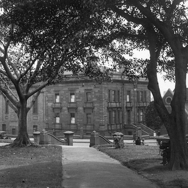 Black and white photo of large school behind trees
