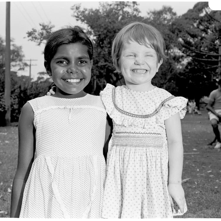 Two girls smiling, one close to each other