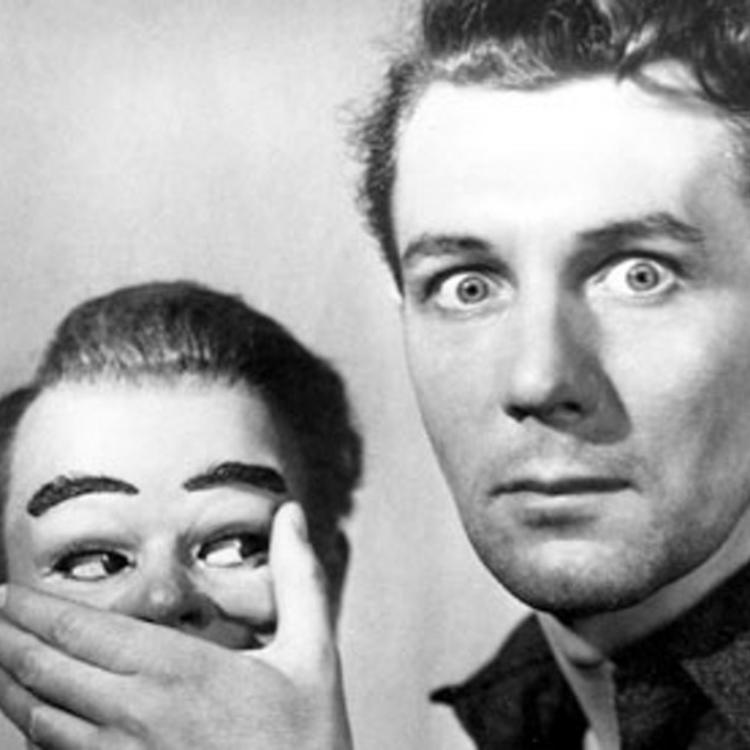 man with a surprised look on his face holding his hand over the mouth of a ventriloquist puppet