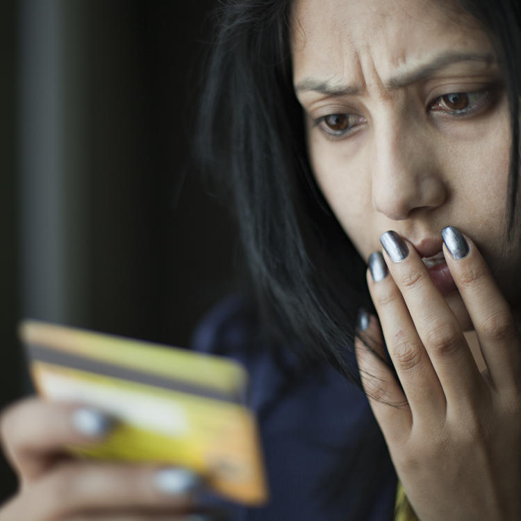 woman looking at credit card with shocked look