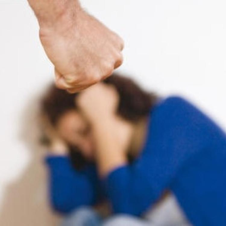 Woman crouching in fear from clenched fist