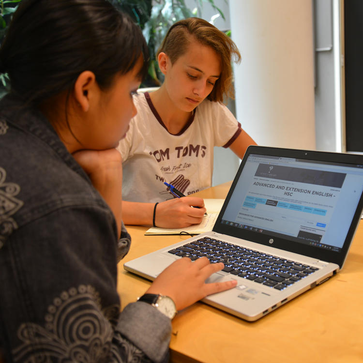 Two students sitting at a desk studying independently with one writing and the other using a laptop