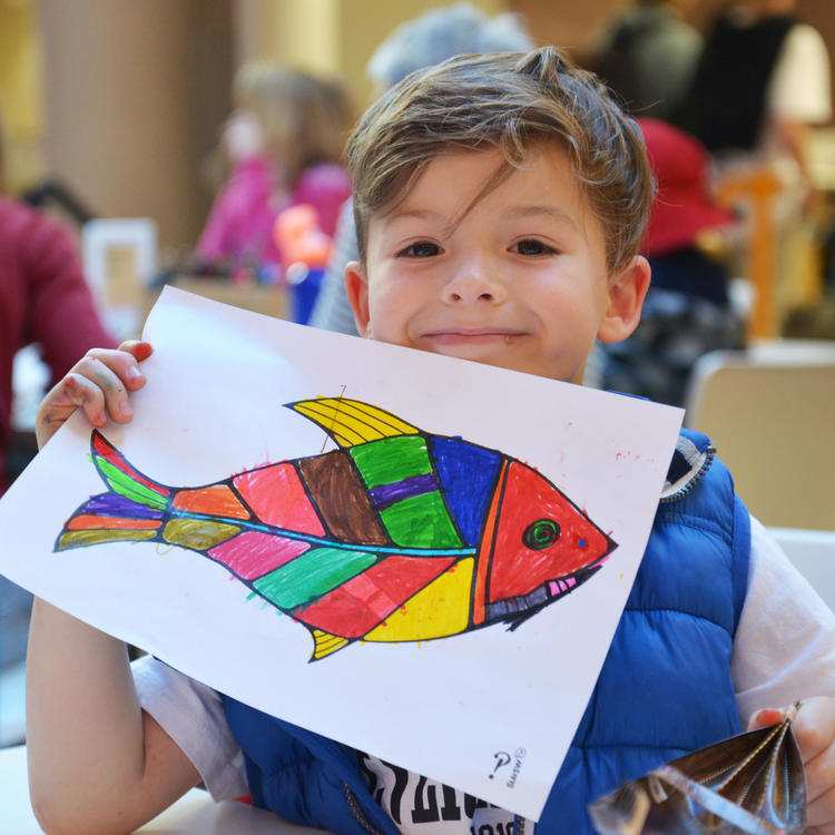 A child holding up a drawing of a fish