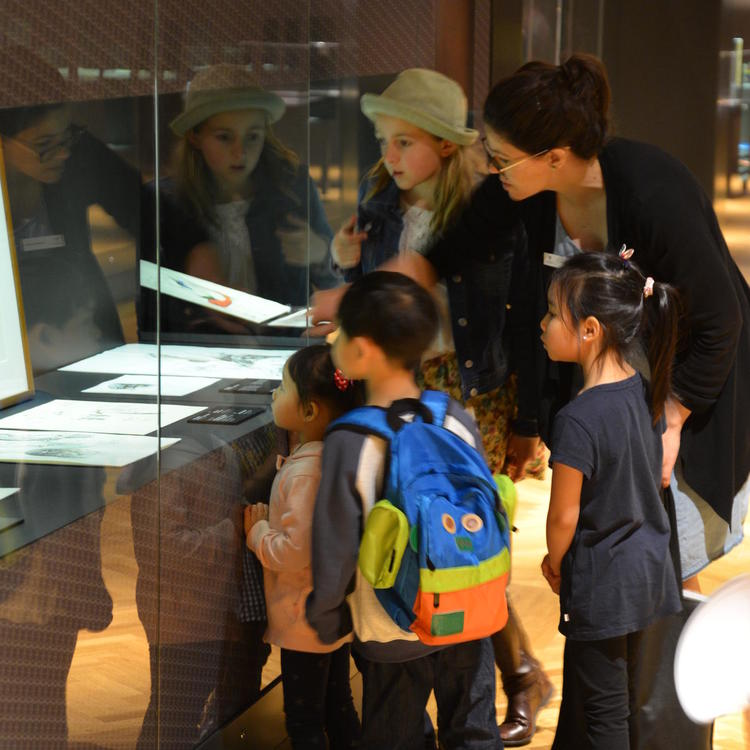 A group of kids looking at an exhibition display