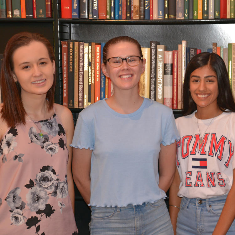 Four students standing in front of a bookshelf