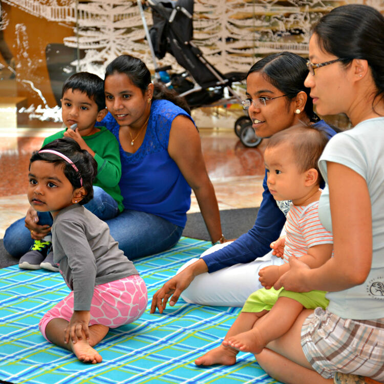 children and mothers sitting on the floor listening to a story