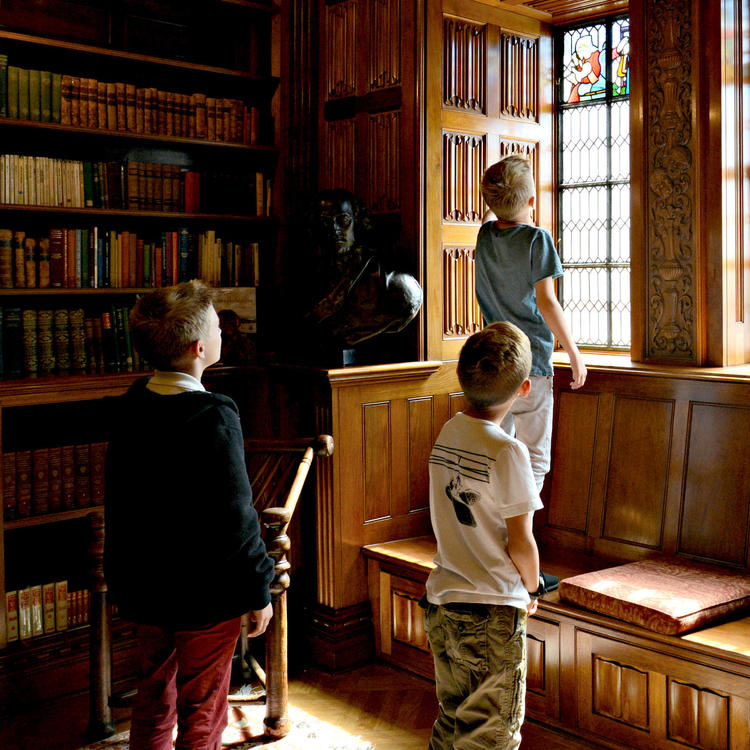 Three boys looking at the stained glass windows in the Shakespeare room at the State Library of NSW.