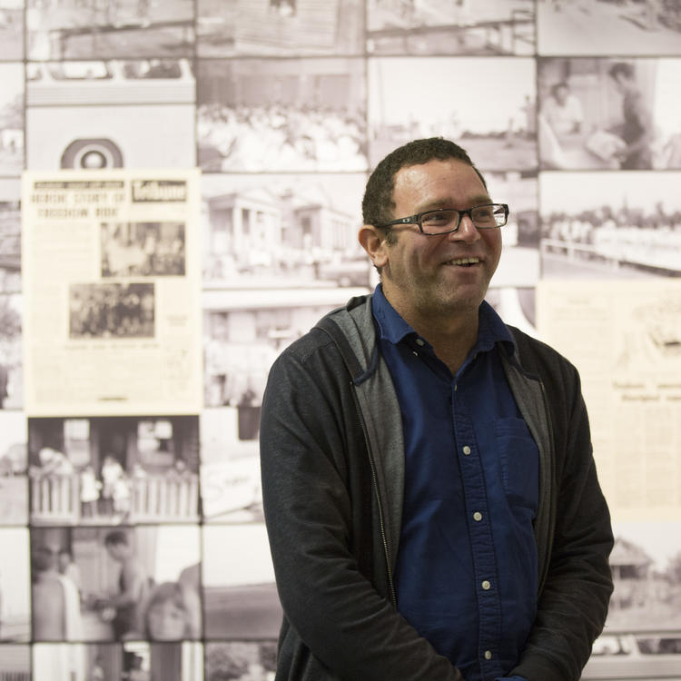 A man smiling at the camera, in front of a wall full of printing