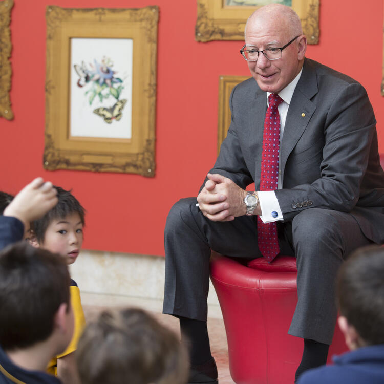 Man talking to a group of children sitting on the floor in front of him