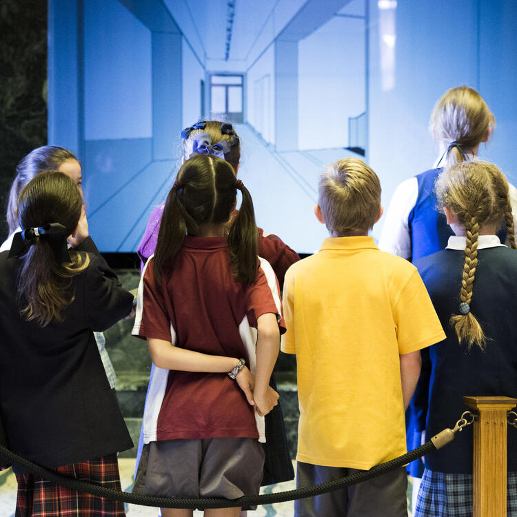 School children looking at a TV screen