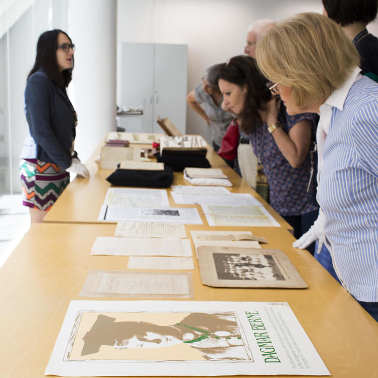 A group of people look over artefacts on a table