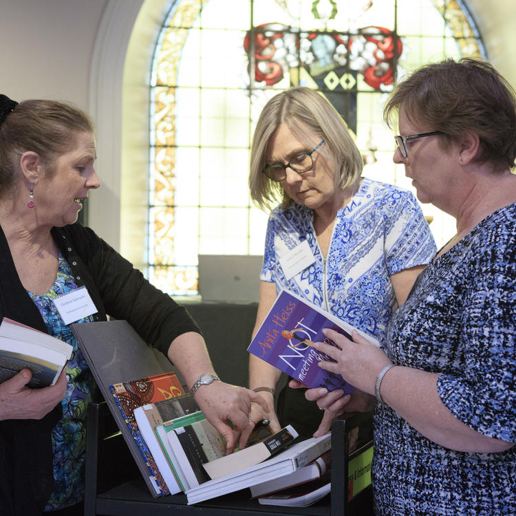 Three women looking at a trolley with books