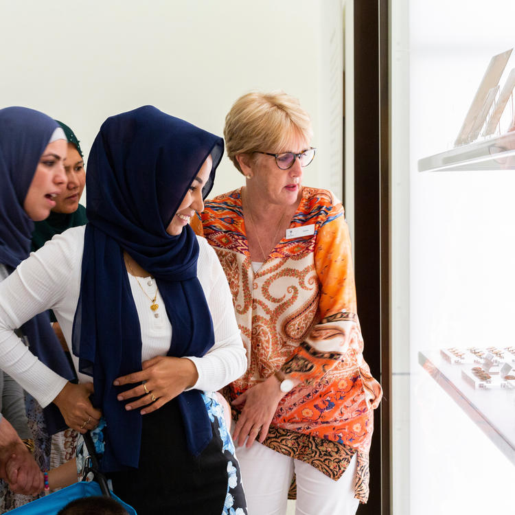 Five women looking into an exhibition case of objects