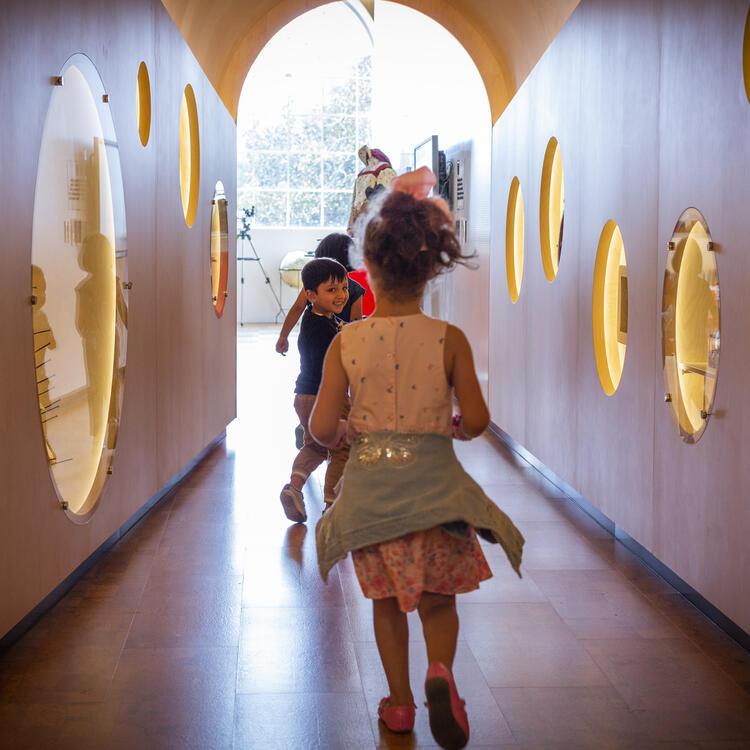 preschool children running down a wood lined  tunnel