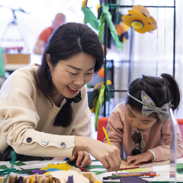 A mother and her young daughter at a craft table.