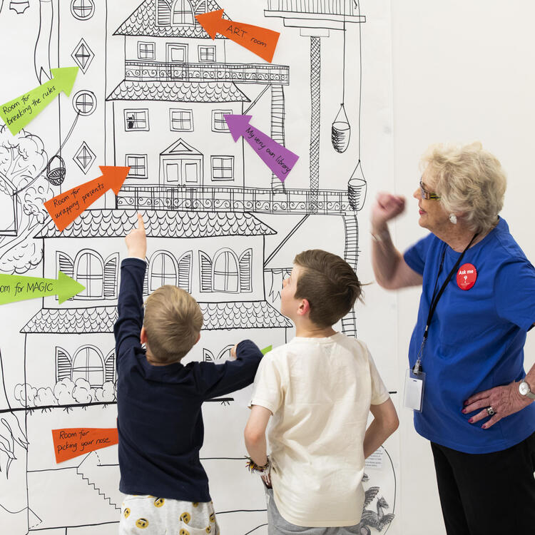 two boys and an adult looking at large image of a building