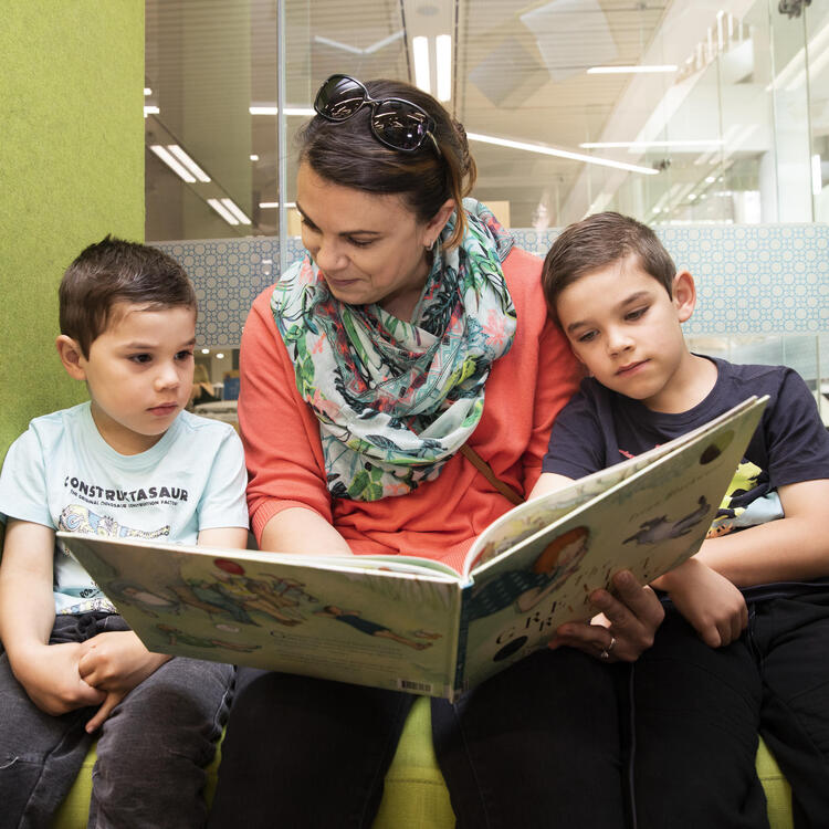 A mother and her two sons reading a book in the Childrens Library