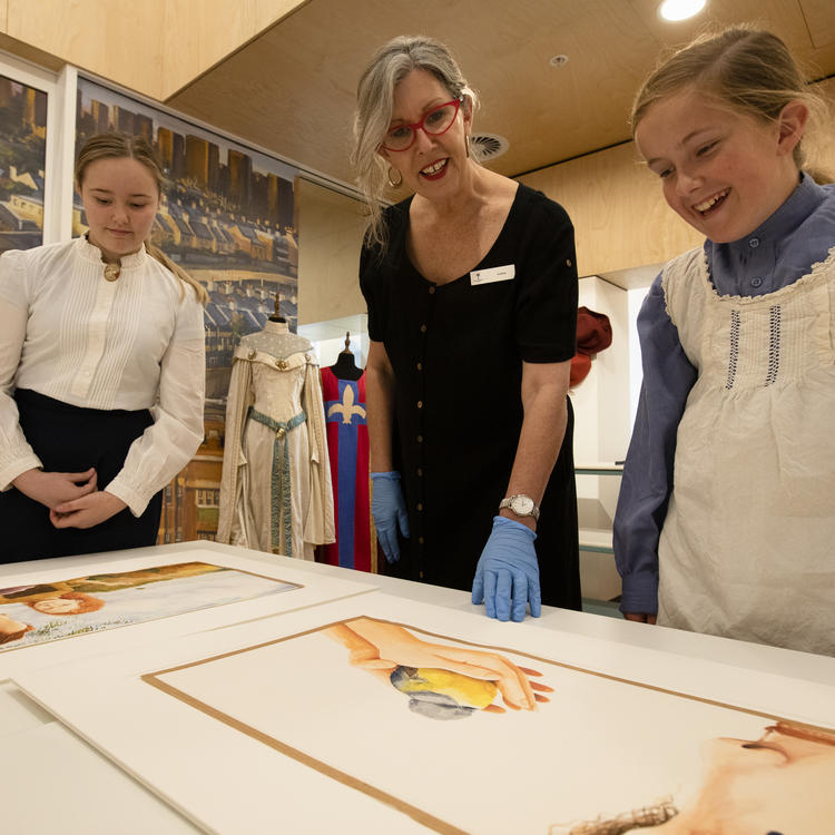 Two girls in costume and a teacher looking at artworks