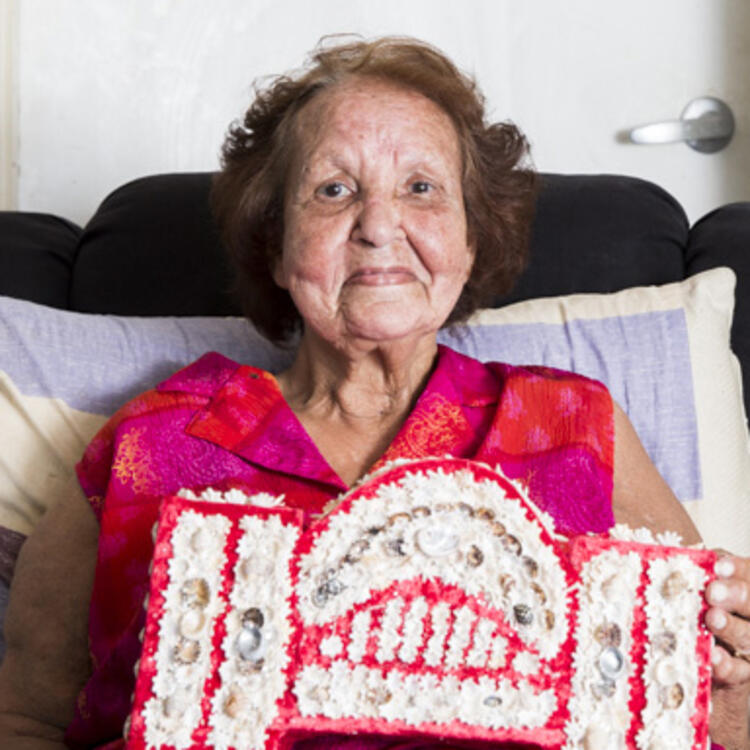 Smiling portrait of an old woman holding a model of the Sydney Harbour Bridge covered in shells.