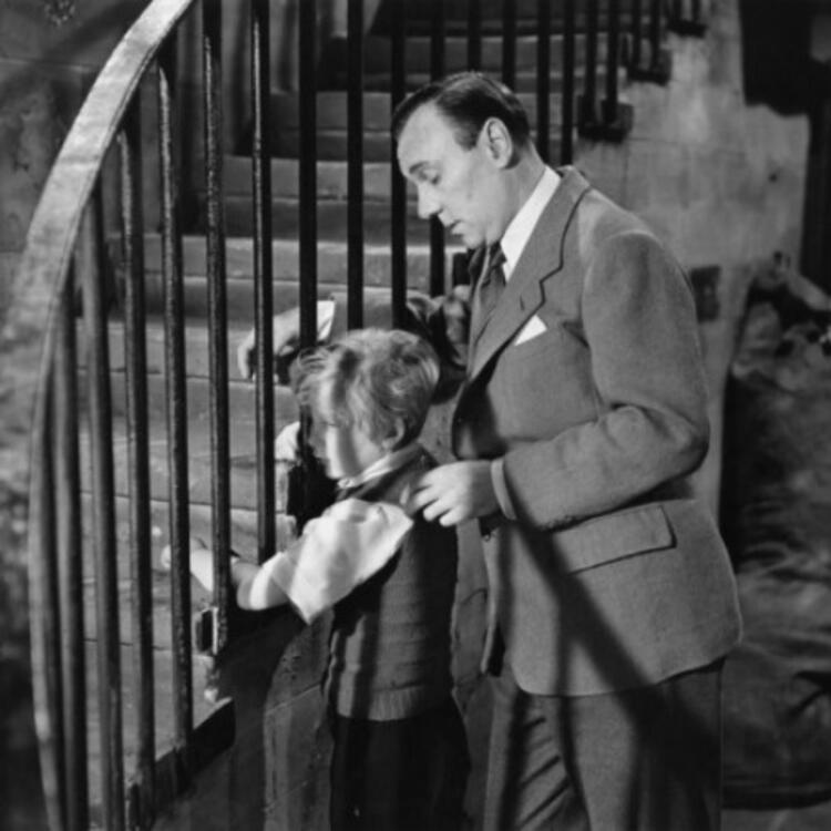 black and white image of a young boy and a man standing at a large staircase