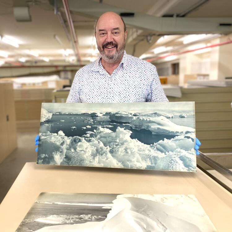 Curator Geoff Barker holding a photo image of ice and water landscape