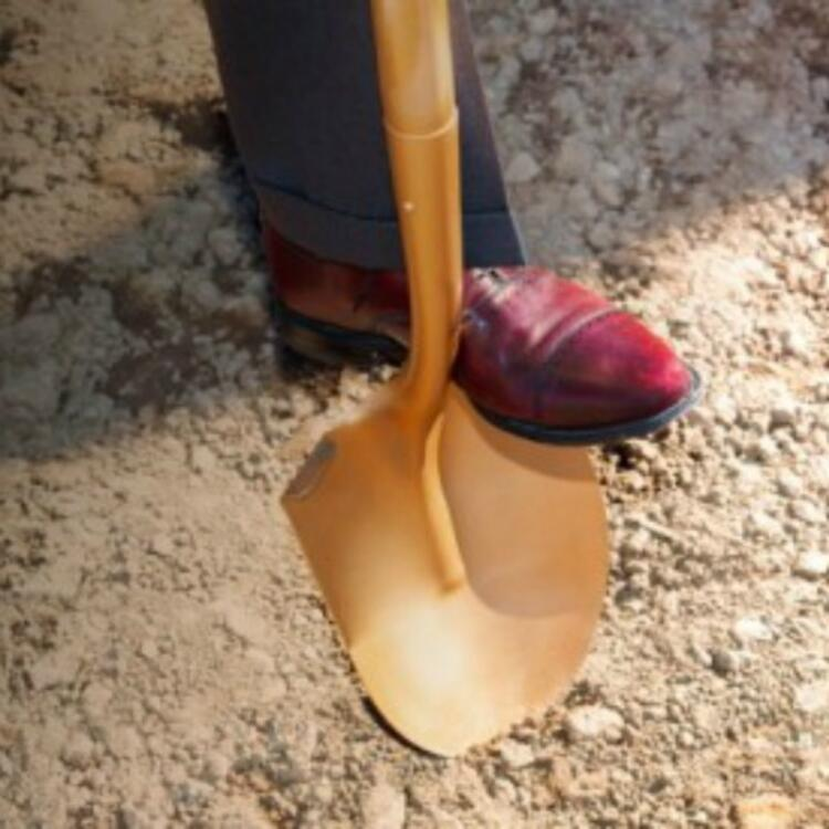 a foot on a shovel above a dirt ground