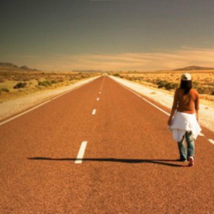 Man walking down a desert road