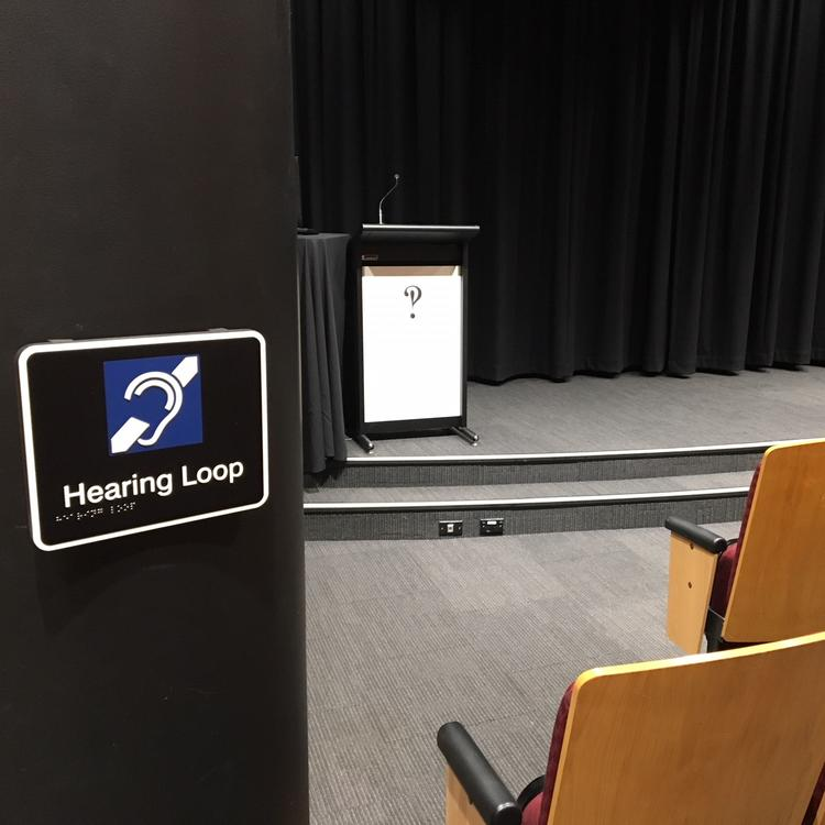 Photograph showing the hearing loop sign in the Metcalfe Auditorium, and the stage area of the room.