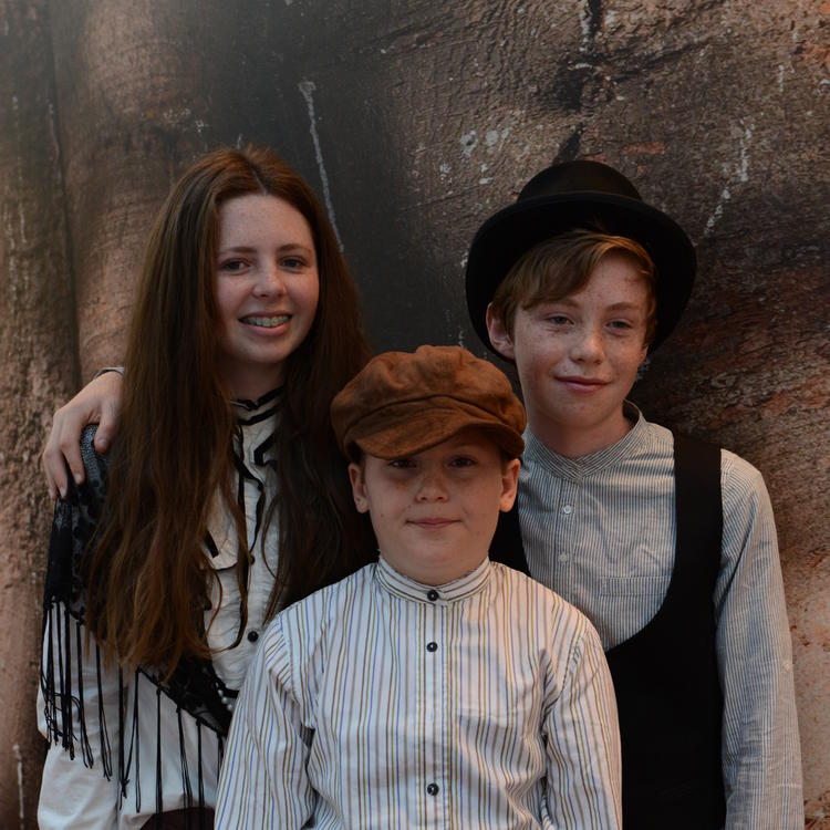Three children in period costume, posing for a photograph