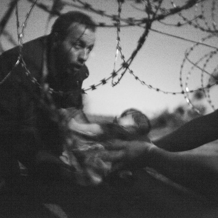 A black and white photograph showing a man passing a baby under a razor wire fence to a person waiting on the other side.