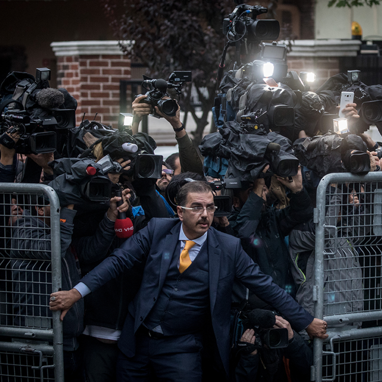 A man opening a gate with a swarm of reporters and photographers behind him.