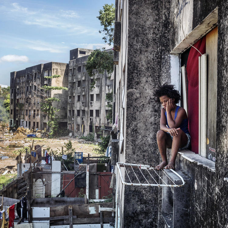 A colour photograph of a boy with a messy afro sitting on a window sill of slum-like apartment building. In the background two similarly abandoned looking buildings sit on the edge of a vacant lot strewn with litter.